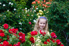 Menina do retrato e arbustos cor-de-rosa Fotografia de Stock Royalty Free