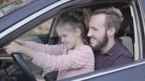 Menina do retrato que senta-se no regaço do pai no fim do carro acima A crian?a est? aprendendo conduzir o carro Homem de sorriso video estoque