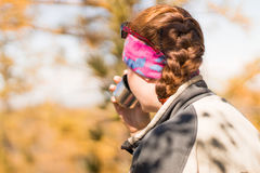 A menina do ruivo bebe o chá de uma garrafa térmica no outono na montanha Foto de Stock Royalty Free