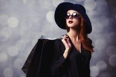 Menina do ruivo com sacos de compras Fotografia de Stock