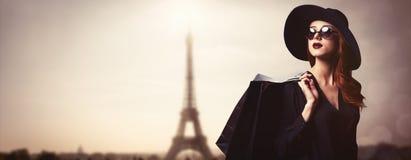 Menina do ruivo do estilo com óculos de sol e sacos de compras fotografia de stock