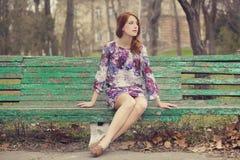 Menina do ruivo do estilo que senta-se no banco foto de stock royalty free