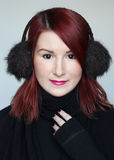 Menina do ruivo em muffs da orelha da pele Foto de Stock Royalty Free