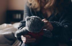 Menina do ruivo em uma cama branca com brinquedo macio Imagem de Stock