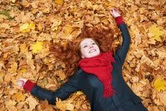 Menina do ruivo que encontra-se nas folhas no parque da cidade, outono Foto de Stock