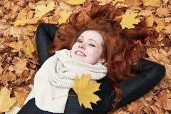 Menina do ruivo que encontra-se nas folhas no parque da cidade, outono Fotografia de Stock Royalty Free