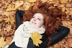 Menina do ruivo que encontra-se nas folhas no parque da cidade, outono Fotos de Stock Royalty Free