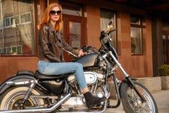 Menina do ruivo que senta-se em uma motocicleta imagem de stock royalty free