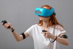 Menina do ruivo que usa vidros de VR sobre o branco Experi?ncia da realidade virtual imagens de stock royalty free