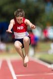 Menina do salto longo do atletismo   Fotografia de Stock