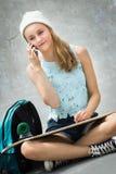 Menina do skater no telefone fotografia de stock