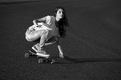 Menina do skater que faz o dowhill fotografia de stock royalty free