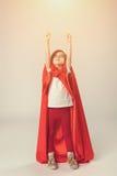 A menina do super-herói no cabo vermelho levantou suas mãos acima imagens de stock royalty free