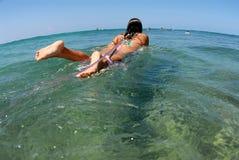Menina do surfista do biquini que rema a OU imagem de stock