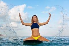 A menina do surfista na prancha tem um divertimento antes de surfar fotos de stock royalty free