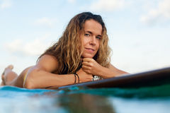 A menina do surfista na prancha tem um divertimento antes de surfar fotografia de stock