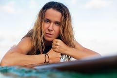 A menina do surfista na prancha tem um divertimento antes de surfar imagens de stock