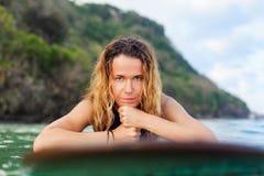 A menina do surfista na prancha tem um divertimento antes de surfar imagem de stock royalty free