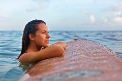 A menina do surfista na prancha tem um divertimento antes de surfar foto de stock
