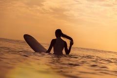 Menina do surfista no oceano no tempo do por do sol Fotos de Stock Royalty Free