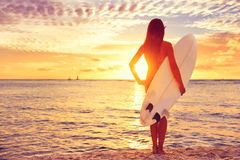 Menina do surfista que surfa olhando o por do sol da praia do oceano Fotografia de Stock Royalty Free