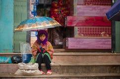 A menina do tribo do monte de Hmong senta-se no mercado com guarda-chuva Imagens de Stock Royalty Free