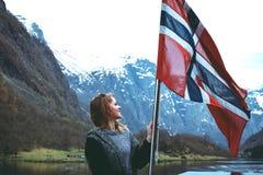 A menina do turista com a bandeira de Noruega aprecia a vista bonita do fiorde e das montanhas Imagens de Stock