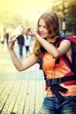 Menina do turista com a trouxa que toma selfies no smartphone fotos de stock