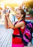 Menina do turista com a trouxa que toma selfies no smartphone imagem de stock royalty free