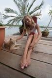 A menina do turista está afagando o gato do gengibre no cais em Koh Panyee foto de stock royalty free