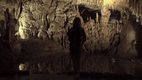A menina do turista está apenas no banco concreto de um rio pequeno da montanha em uma caverna de pedra video estoque
