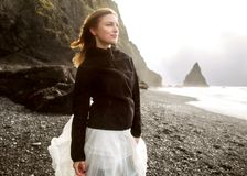 A menina do turista está estando na praia no por do sol fotografia de stock royalty free