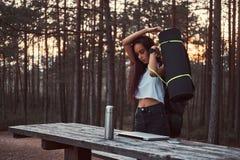 A menina do turista está indo ir mais após uma ruptura na floresta bonita do outono durante o por do sol imagem de stock