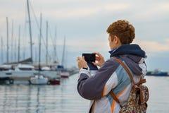 A menina do turista está tomando a foto em seu telefone celular fotografia de stock