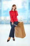Menina do turista que senta-se em uma mala de viagem Imagens de Stock Royalty Free