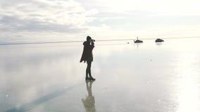A menina do turista toma uma foto do lago congelado vídeos de arquivo