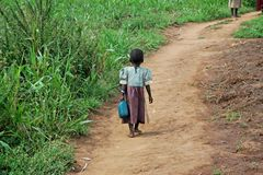 A menina do Ugandan leva Jerry Can On um trajeto da sujeira Imagem de Stock Royalty Free