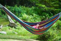 Menina do verão no hammock que joga com um telefone de pilha Fotografia de Stock Royalty Free