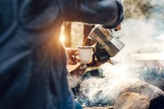 A menina do viajante derrama-se bebida quente nas montanhas pr?ximo ao por do sol da fogueira a tempo fotos de stock royalty free