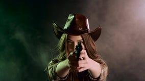 A menina do xerife guarda um revólver em suas mãos e em visar o bandido Fundo preto do fumo Movimento lento filme