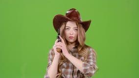A menina do xerife guarda um revólver em suas mãos e em visar o bandido Tela verde vídeos de arquivo