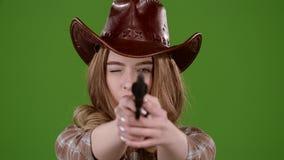 A menina do xerife guarda um revólver em suas mãos e em visar o bandido Tela verde Movimento lento vídeos de arquivo