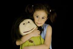 A menina doce abraça sua boneca favorita Foto de Stock