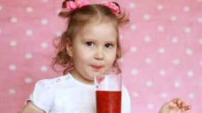 A menina doce bebe o batido da framboesa e sorri Bebida do vegetariano Retrato do close-up de uma criança que aprecie a video estoque
