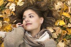 A menina doce bonita encontra-se para baixo sobre as folhas de outono Imagem de Stock