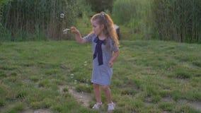 A menina doce bonito funde bolhas e joga fora no gramado verde com grama filme