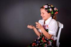 A menina doce borda com uma agulha que senta-se em uma cadeira imagens de stock