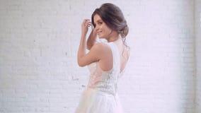 Menina doce com cara do bebê e voltas macias das características no vestido branco luxuoso elegante longo, um penteado delicado d filme