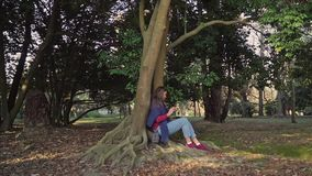 A menina doce com o telefone em suas mãos está sentando-se sob a árvore grande com torção das raizes que crescem fora filme