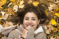 A menina doce de sorriso encontra-se para baixo sobre as folhas de outono Fotografia de Stock Royalty Free